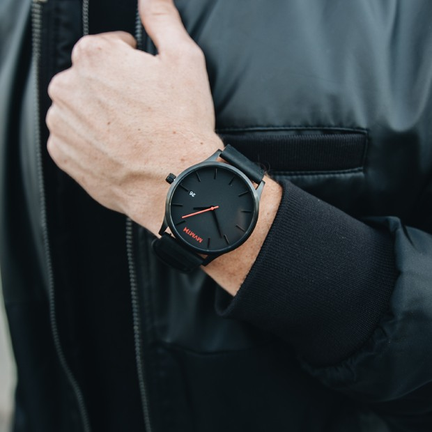 a black leather watch on a mans wrist