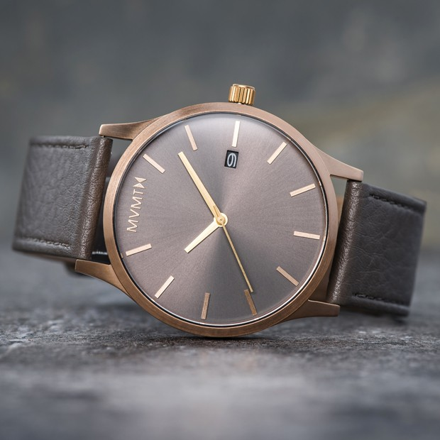 bronze and grey leather watch on a grey surface