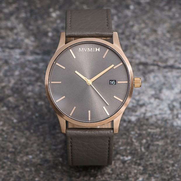bronze and grey leather watch on a flat surface