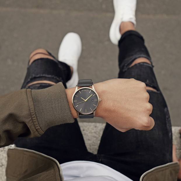 bronze and grey leather watch on a mans wrist