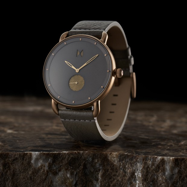 bronze and grey leather watch on a dark surface