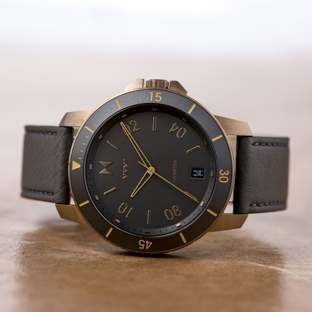 bronze and grey leather watch on a beige surface