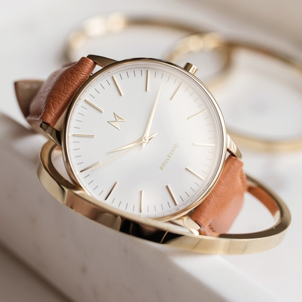 white, gold and orange leather watch on a white surface