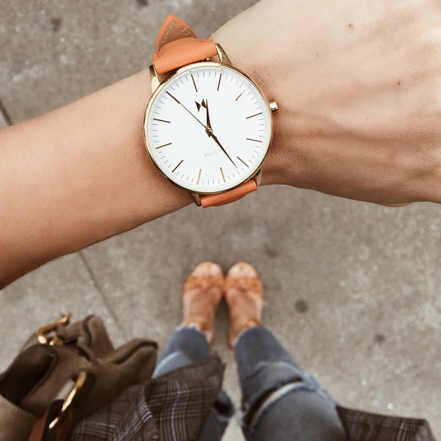 white, gold and orange leather watch on a womans wrist