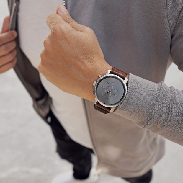 gunmetal and chestnut brown leather watch on a mans wrist
