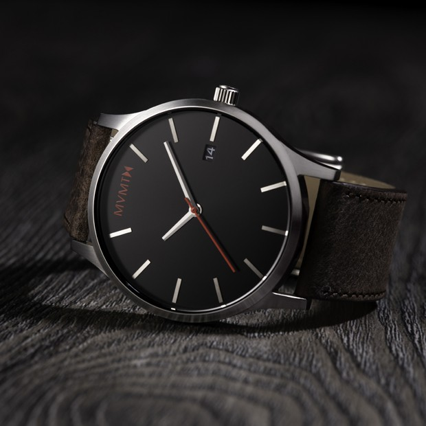 brown leather watch with a black face and silver case on a wood background
