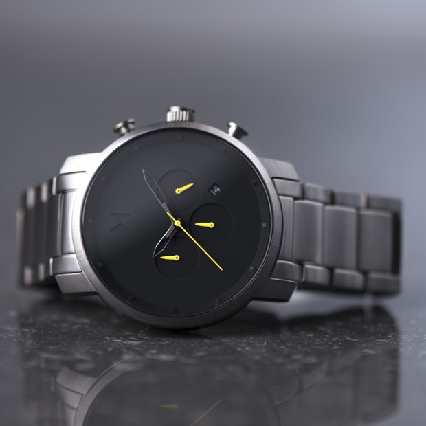 black and silver link watch with yellow features on a grey background