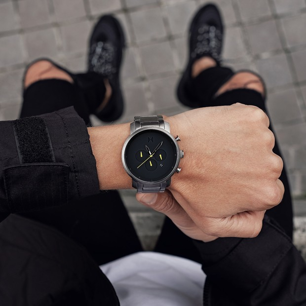 black and silver link watch with yellow features on a mans wrist