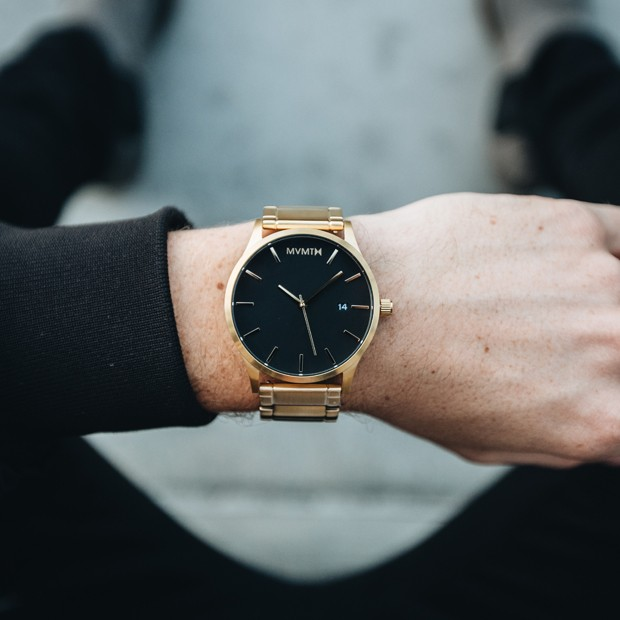 black and gold watch on a mans wrist