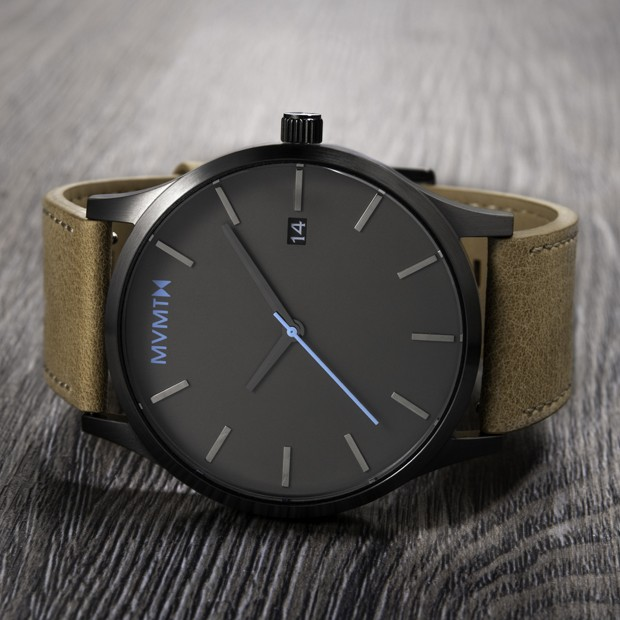 gunmetal and sandstone leather watch on a wood surface