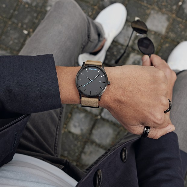 gunmetal and sandstone leather watch on a mans wrist
