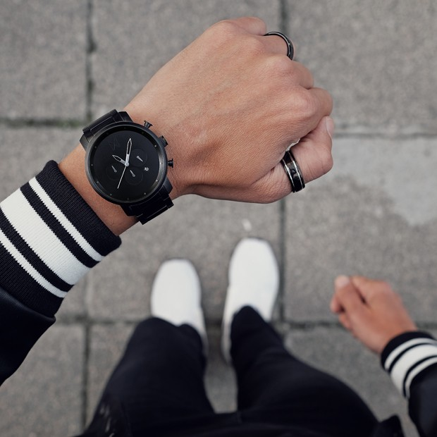 all black link watch on a mans wrist
