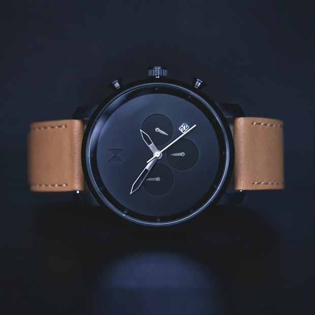 black and tan leather watch on a black background