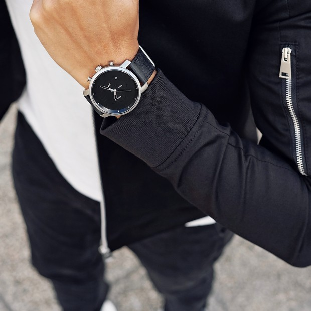 silver and black leather watch on a mans wrist
