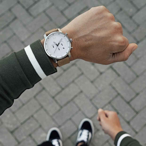 white silver and tan leather watch on a mans wrist
