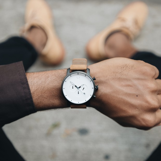 white black and tan leather watch on a mans wrist