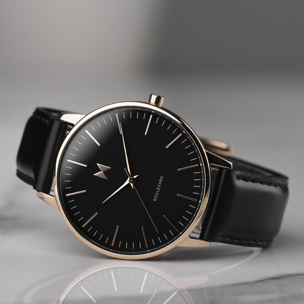 rose gold and black leather watch on a white surface