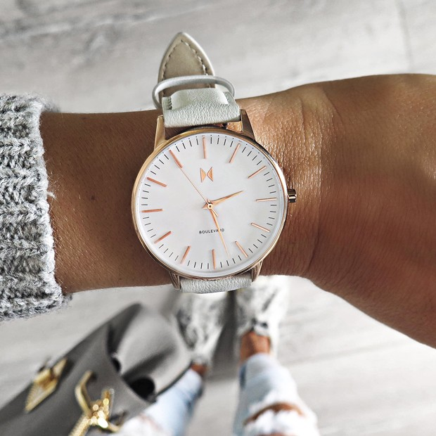white, rose gold and light grey leather watch on a womans wrist