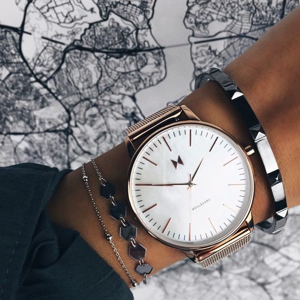 rose gold stainless steel watch with pearl face on a womans wrist