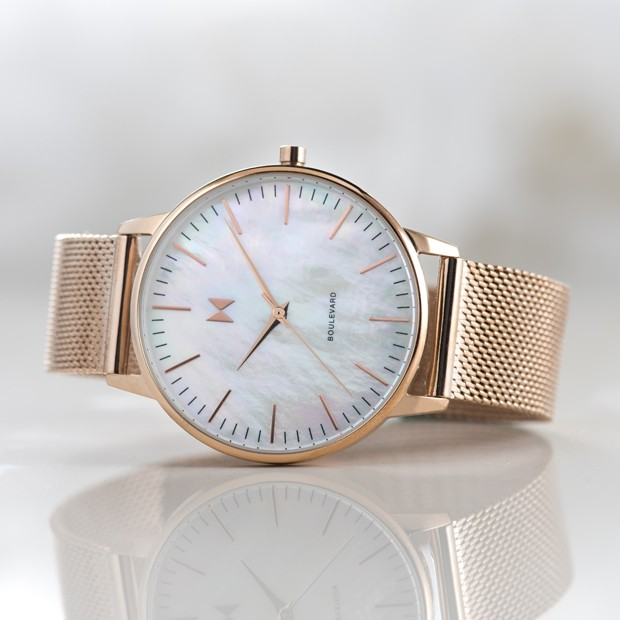 rose gold stainless steel watch with pearl face on a white surface