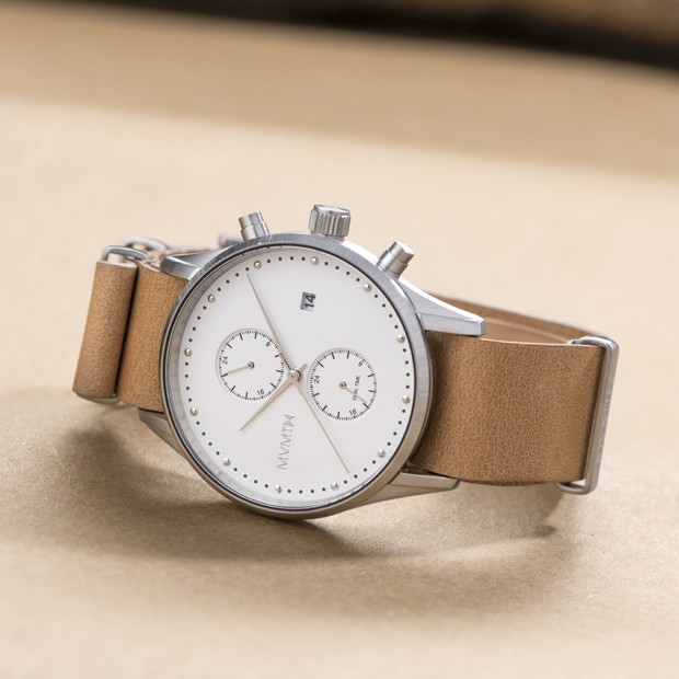 white and tan leather watch on a beige background