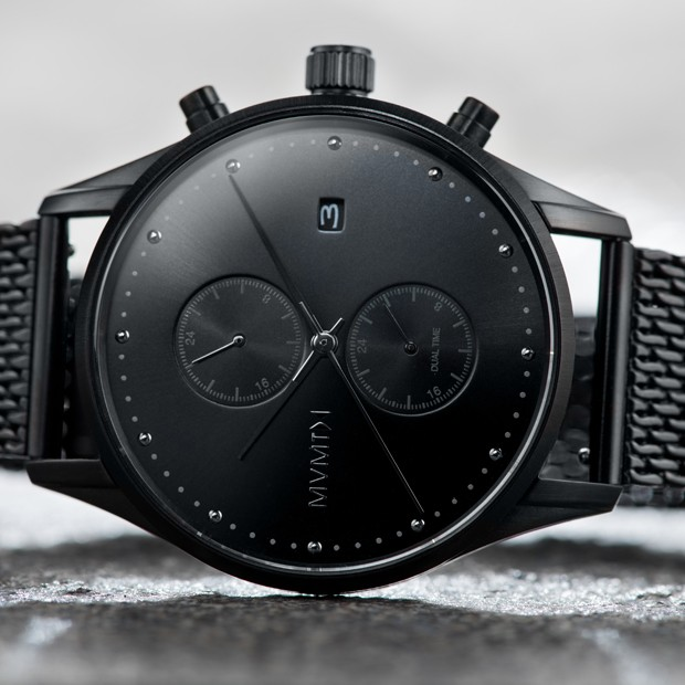 all black stainless steel watch on a grey surface