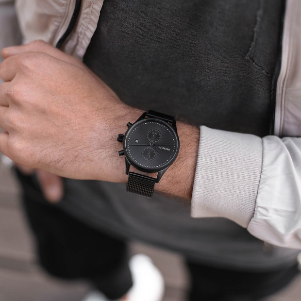 all black stainless steel watch on a mans wrist