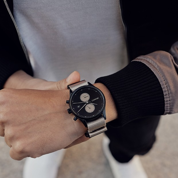 black and tan nylon watch on a mans wrist