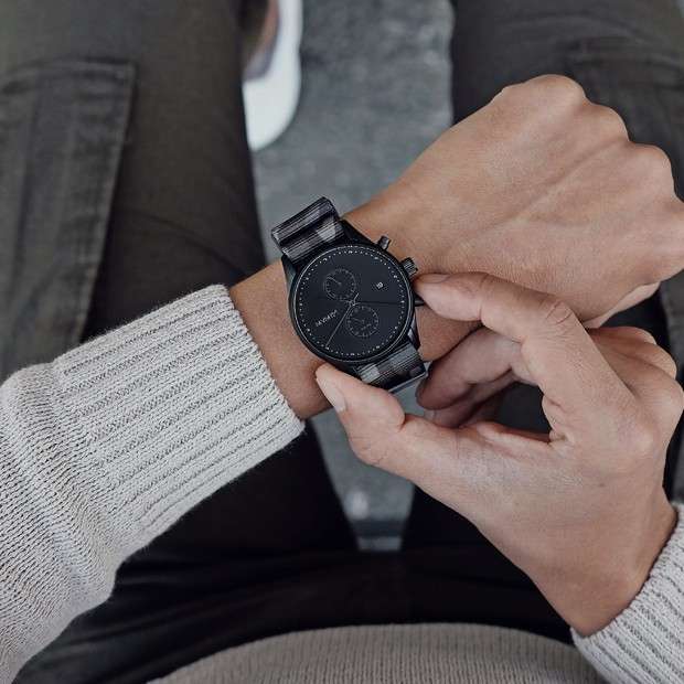 black watch with camouflage nylon strap on a mans wrist