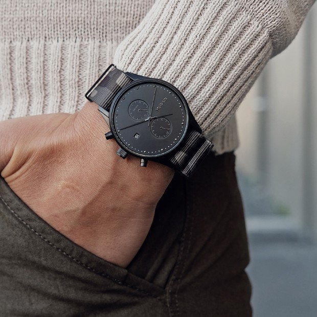 black watch with camo nylon strap on a mans wrist