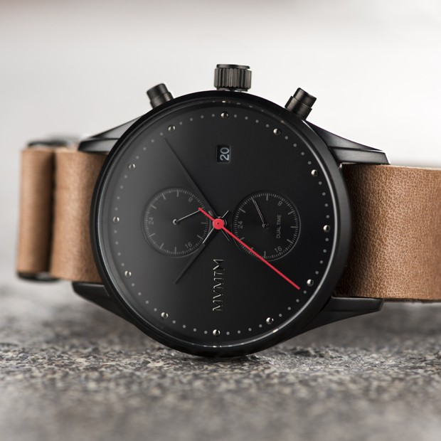black and tan leather watch on a grey background