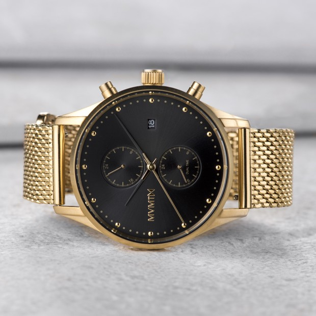 black and gold mesh watch on a grey surface