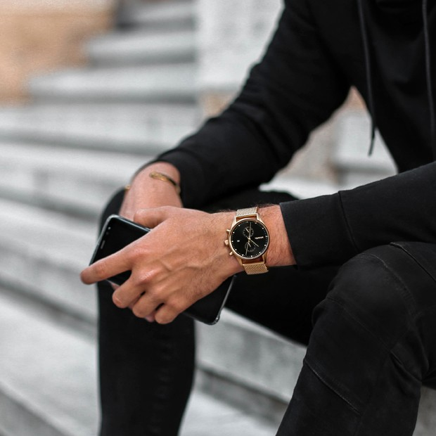 black and gold mesh watch on a mans wrist