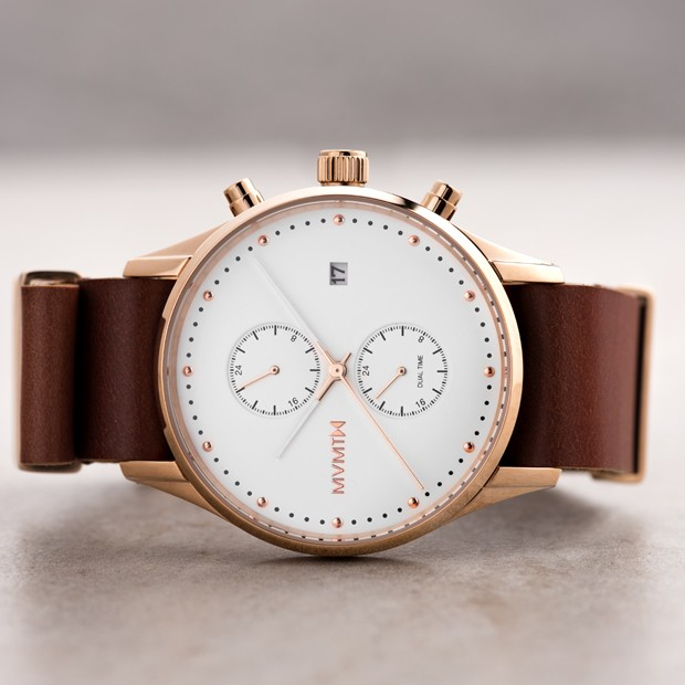white rose gold and tan leather watch on a beige surface