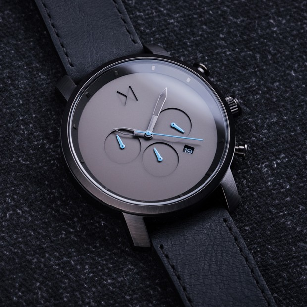 gunmetal and black leather watch on a black background