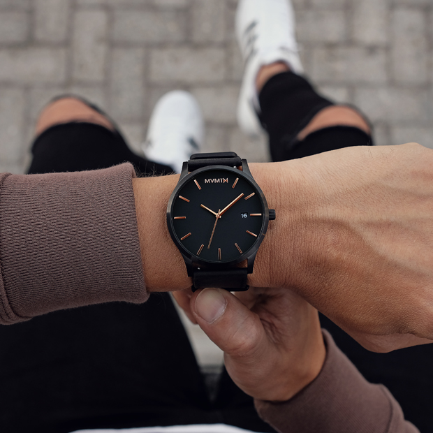 black leather watch with rose gold features on a mans wrist
