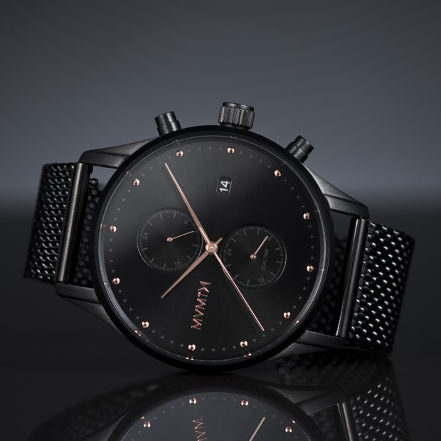 black stainless steel watch with rose gold features on a black surface