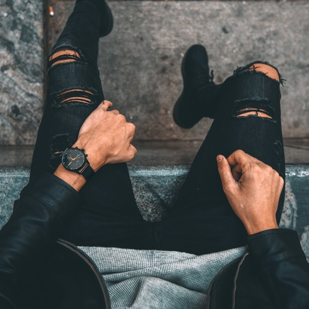 black stainless steel watch with rose gold features on a mans wrist