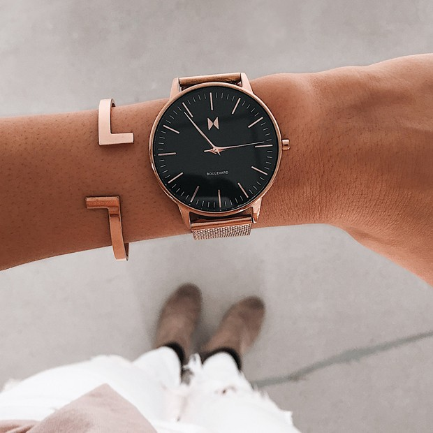 black and rose gold stainless steel watch on a womans wrist