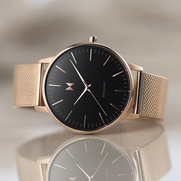 black and rose gold stainless steel watch on a white surface