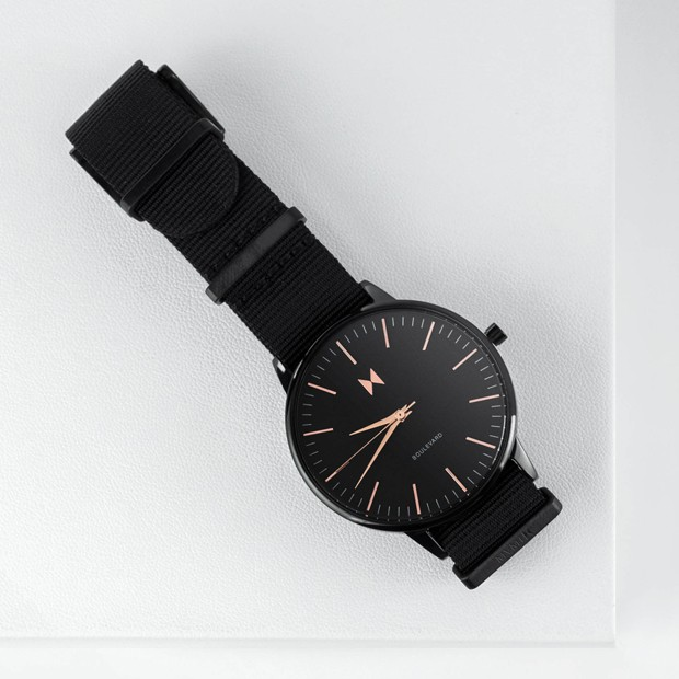 all black nylon watch with rose gold features on a white surface