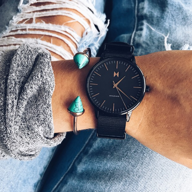 all black nylon watch with rose gold features on a womans wrist