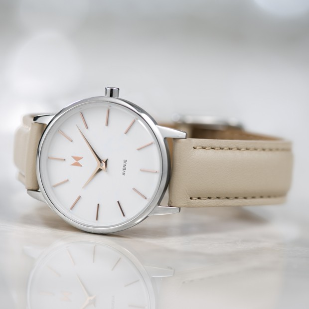 white silver and nude leather watch on a white surface