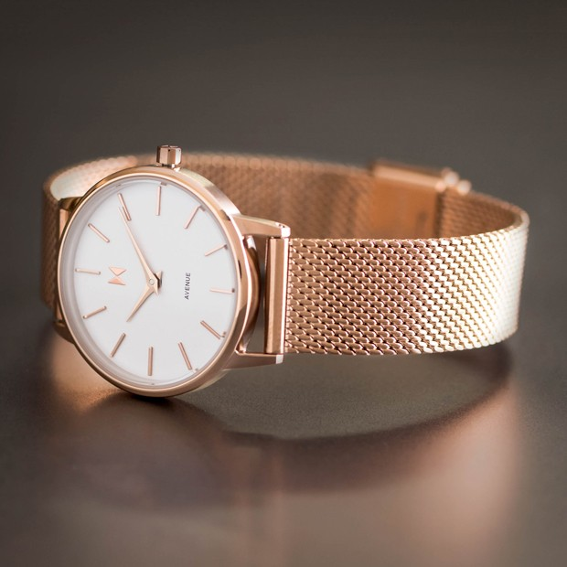 white and rose gold stainless steel watch on a dark surface