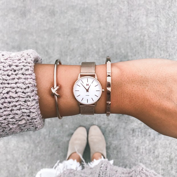 white and rose gold stainless steel watch on a womans wrist