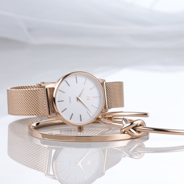 white and rose gold stainless steel watch on a white surface with rose gold bracelets