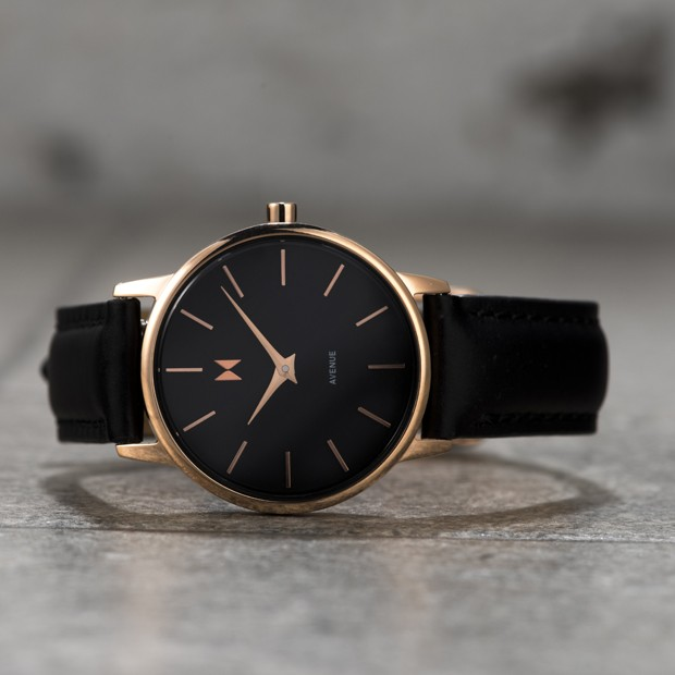 rose gold and black leather watch on a grey surface