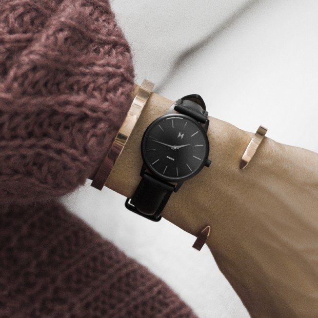 all black leather watch on a womans wrist