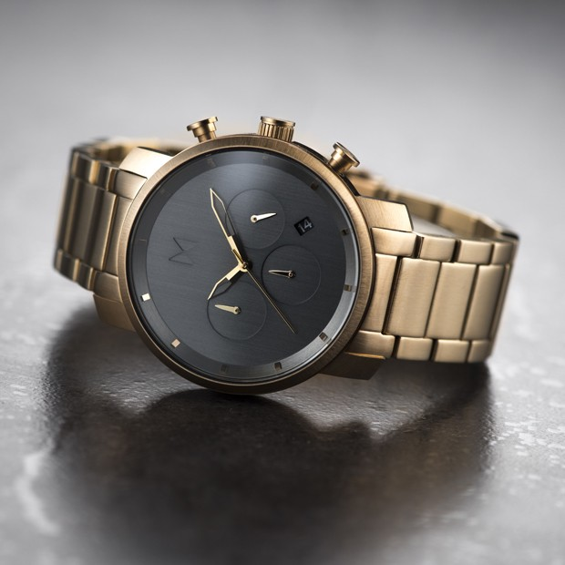 bronze link watch with sage face on a grey surface