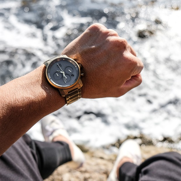 bronze link watch with sage face on a mans wrist
